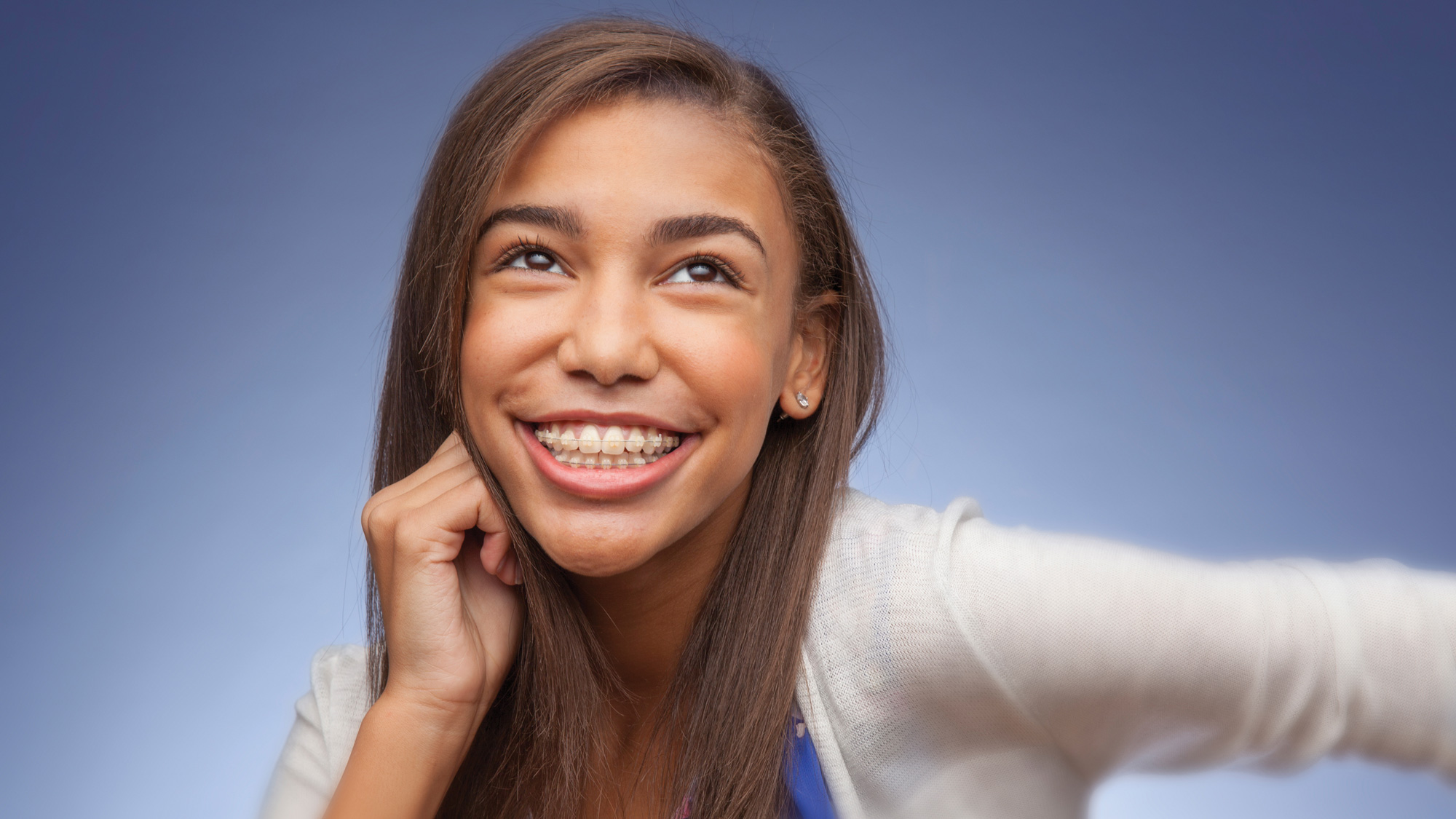 A young woman smiling while wearing braces. She's looking above the camera.